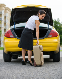 Female passenger loading her things to the taxi's trunk